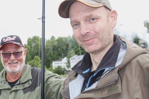 FLAKS: Rune Skoglund fra Krokstadelva kan smile fornøyd. For fem minutter etter at dette bildet ble tatt, og rett før han skulle pakke sammen utstyret, fikk han jammen en laks til på kroken. Nils Skoglund ser seg slått som storfisker, og gir sønnen en klapp på skuldra.