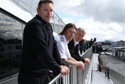 F.v. matros Roy Døskeland, maskinsjef Lennie Mathiesen og kaptein Arvid Langeteig er alle stolte over å jobbe på det Langeteig beteiknar som framtida på norske fjordar.