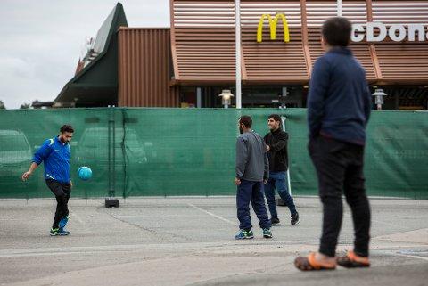 KOMMER FÆRRE: En gruppe asylsøkere spiller fotball utenfor mottakssenteret for flyktninger og immigranter i Råde. Senteret ligger i Smart Clubs tidligere lokaler rett ved E6 og har McDonalds som nærmeste nabo. Foto: Tore Meek (NTB Scanpix)