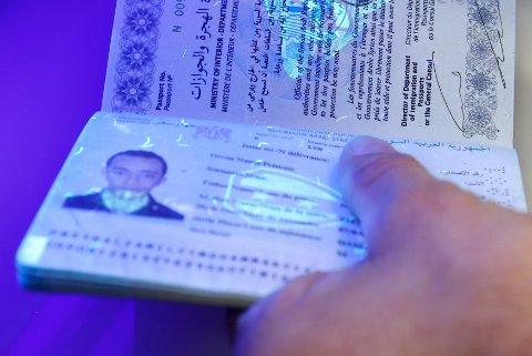 Ved hjelp UV-lys blir et pass sjekket ved et flyktningesenter i Tyskland. For dem som har pengene er det mye greiere å kjøpe et pass enn å forfalske.