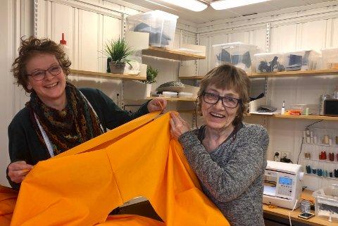 ORANSJE: Helsepersonellet vil lyse opp i hverdagen når de ifører seg sine nye beskyttelsesfrakker. Caroline Godijn og Inger Marie Kjexrud driver serieproduksjon på systua i Kaffegata.