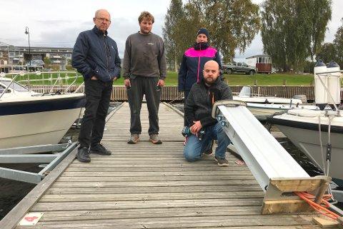 STORE SKADER: Tom Bråthen (f.v.), Ole Henrik Sæter, Kristin Myrvang og Kenneth Berntsen med en av de ødelagte strøm- og vannstolpen, som nå er dratt opp på land.