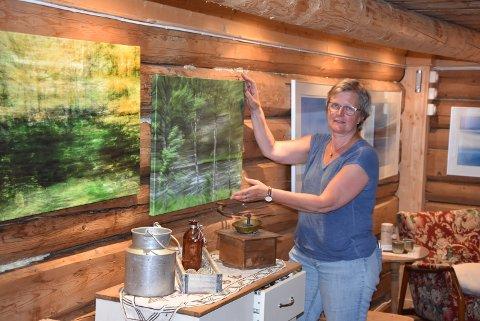 Spennende omgivelser der Lene henger opp bildene på de gamle tømmerveggene.