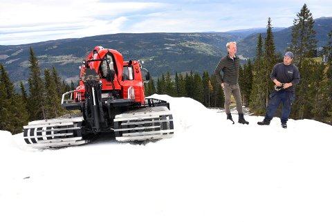 """Kvitfjell Alpinanlegg har lagret snø gjennom sommeren. Nå legger de snø for å sikre en rekordtidlig åpning. Daglig leder i alpinanlegget Odd Stensrud og """"snøutpakker""""  Eivind Dahl på den store snøhaugen som ligger ved maelomstasjonen i Kvitfjell."""