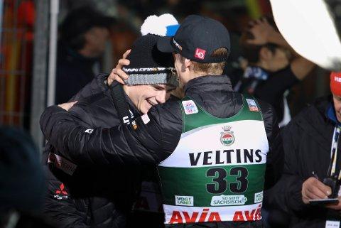 Marius Lindvik t.v. gratuleres av Robert Johansson under hopp stor bakke individuell i verdenscupen for menn i Klingenthal i Tyskland.