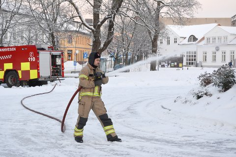 KALDT: Petter Salamonsen fra Halden brannvesen sprøytet 8000 liter vann utover i Busterudparken mandag formiddag. - Håpet er at det skal fryse fort slik at det ikke renner nedover gågata, sier han.