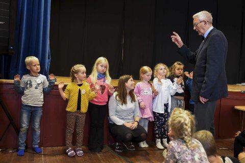 DEMONSTRERTE: Oddmund Hus, den aller fyrste skulestyraren, fekk med seg 1.-klassingane på å visa kor mange år Kinsarvik skule er.