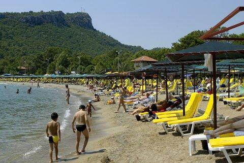 Turister ligger og soler seg på stranden i Kemer.