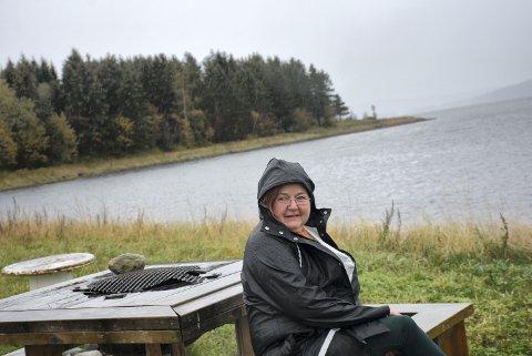 PÅ KAUSVOLLEN: Heidi Iren Skaanes på en av benkene på friområdet ved Kausbukta og Kaustangen (bak).