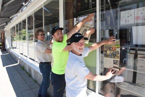 I GANG: Svein Holthe (t.v), Asmund Saure Hagen og O. Anders Hagen skal henge opp bilder, postere og platecovre av 20 Levanger-band i vinduerne til Salong Michel i Brugata.