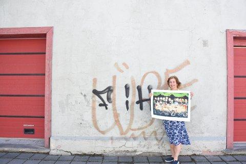 NY VEGG MALES: Denne veggen av den gamle brannstasjonen i Kirkegata foran Fenka, skal snart prydes av et nytt veggmaleri signert kunstneren Ståle Gerhardsen. Dette som et ledd i separatutstillingen han skal ha på Galleri Fenka. Elsabeth Ben Riala med et av utstillingenes malerier.
