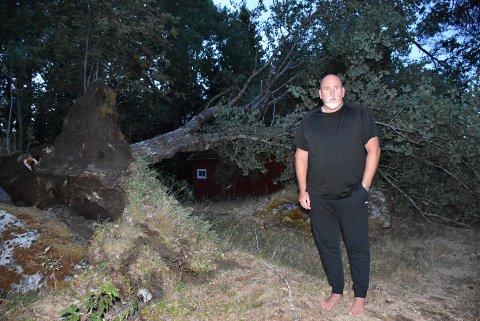 – Elverket har gjort en kjempejobb og reddet bryllupsfesten vår, sier Stein Henriksen fra Setskog og viser fram et stort tuntre som blåste overende bak huset. Det forteller litt om kreftene som var i sving fredag. Foto: Trym Helbostad