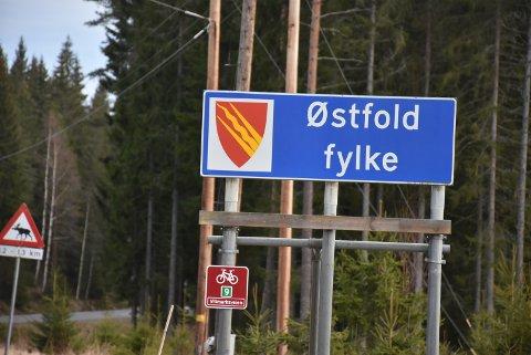 Skiltet med Østfold fylke langs fylkesvei 21 har fått henge i fred, mens skiltet som var plassert under, Rømskog kommune, er fjernet. Foto: Trym Helbostad