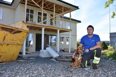 Snart ferdigbygd: Jon Arne Ullerud (38) sammen med hunden Nikki på branntomta i Aurskog. Bolighuset er snart bygd opp igjen, og Ullerud kan flytte hjem i slutten av august.