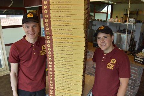 Petter Bjerke (t.v.) og Mikael Kjus i Pizzabakeren Bjørkelangen har travle dager. Det er ikke få slike esker med varm pizza som forlater lokalet.