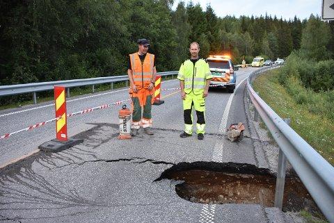 Tore Dyrseth (t.h.) fra Viken fylkeskommune og Thor Arne Carlsson fra PEAB foran synkehullet på fylkesvei 170 ved Eidsdammen mandag kveld. Foto:Trym Helbostad