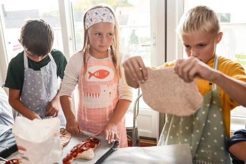 Tobias (9), Daisy (8) og Benjamin (9) i full gang med å lage pizza.