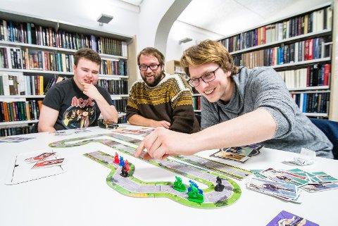 INNSPURT: Håvard kaster seg frem i feltet på sykkelspillet Flamme Rouge, mens Ørjan og Sivert følger spent med.