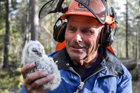 KATTUGLE: Øyvind Fosse med en rundt tre uker gammel kattugle. Nå skal den snart få ring rundt beina.