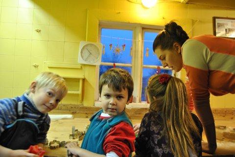 Simen Holtan Larsen og Sander Johansen har sett nissen i år, og kan beskrive han. Bak står Andrea Nilsen og hjelper de unge bakerne.