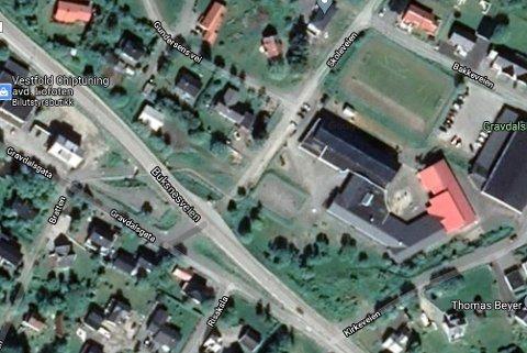 Oversiktsbilde med Buksnes skole til høyre. Dagens busslomme i Buksnesveien samt undergangen til Gravdalsgata går fram av bildet. Den nye avstigningssonen vil ligge ved Gravdalsgata, slik at busspassasjerene kan stige like ut av bussen til gangveien under Buksnesveien og videre.