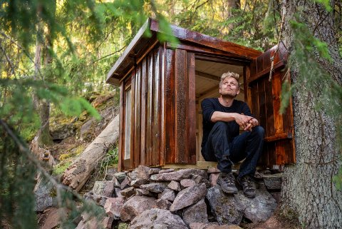 HYTTEJEGER: Forfatter Marius Nergård Pettersen i en av de hemmelige hyttene han har funnet. (Foto: Dal Forlag)