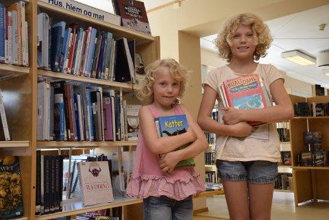 Leselystne: Storesøster Ingrid Opdal (t.h.) og Maria Opdal er glad i eventyr og historier, og begge forsynte seg godt i hyllene i fjor. Bildet er fra Hole bibliotek sommeren 2016.