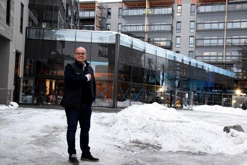 Usjenert: Salgsdirektør Ståle Hjerpseth foran boligkomplekset på Brutorget. Han påpeker hvor usjenert felles uteområdet på taket blir (hvor det er plast hengende over gjerdet).