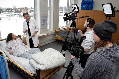 """Engasjerte: Faglærer på medier og komminikasjonslinja Egil S. Granum (ikke på bildet), sier han merker at elevene blir mer engasjert når de vet det blir brukt til noe, og ikke bare er en skoleoppgave. Fra venstre: Fagutviklingssykepleier og """"skuespiller"""" Eva Marie Vestby, nevrolog og medisinsk ansvarlig for slagavdelingen på Drammen sykehus, Karl Friedrich Anthor, samt medier- og kommunikasjonselevene Jonas Graniero Thue og Trond Anders Nordby."""