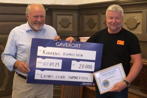 FIKK PRIS: Kirkens Bymisjons Jon Gulbrandsen fikk overrakt sjekk og diplom fra president i Lions Club Hønefoss, Svein Oppegaard, på klubbens medlemsmøte denne uken. Foto: Privat
