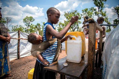 FÅR RENT VANN: Ndoya Konga kan hente vann sammen med sin ni måneder gamle lillesøster på ryggen takket være hjelp fra Kirkens Nødhjelp. I Louva i Angola ved grensen til Kongo bygger de opp en leir for flyktninger fra Kasairegionen i Kongo.