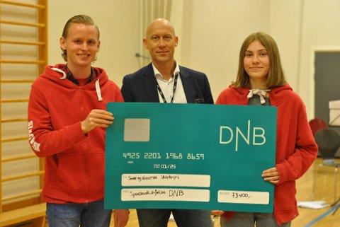 Isak Tveita Andersen og Celina Trevland mottok på vegne av korpset en sjekk fra Simen Smith Ringdal fra Sparebankstiftelsen DNB.