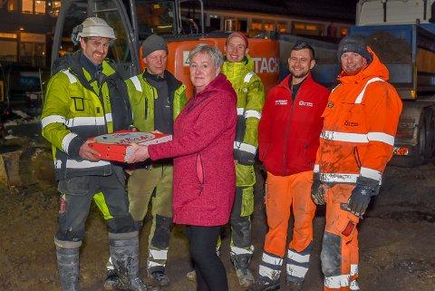 Hans Magnus Kjos (37, f.v.), Morgan Rakstad (32), Jesper Dramstad (19), Michut Sokolowski (28) og Pavel Budnik (26) fikk rykende varm pizza av Ann-Kristin Enger (55). Hun mener de fem står sånn på med Skjønhaug torg, at det fortjener en oppmuntring.