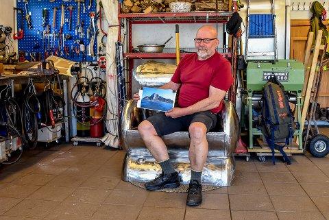 Benken han sitter på er laget av fem varmtvannstanker. Ryggen på benken har profilen til Rødøyløva, det er det samme fjellet som han holder opp et bilde av. Nå skal benken få et sete før den sendes opp til Klokkergården, pensjonatet ved foten til Rødøyløva.