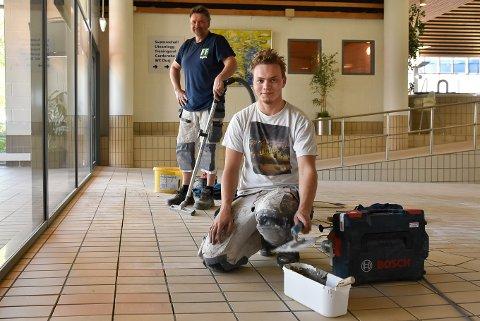 FIKSER FLISENE: Magnus Huuse (21) og Hans Såstad fra Smaadahl er i gang med å fikse flisene til badet åpner igjen.