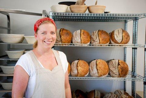 AVKJØLES: Her står Eva Solerød (33) sammen med de nystekte brøda. De står her til avkjøling før de puttes i fryseren.