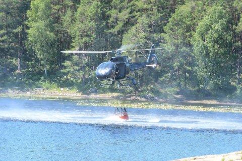 Hentet vann: Brannhelikopteret i ferd med å hente vann fra et tjern i nærheten.