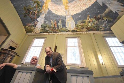 VÅR HERRES TJENERE: Sogneprestene Terje Nyvoll og Rune Lia lar seg imponere av den lille, vakre kirken i Lisleherad som har juleevangeliet malt i taket. Perfekt for å få den gode julestemningen.
