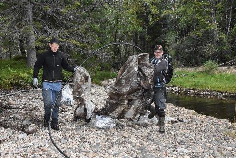PRESENNING: Thomas Lien og Hans Karlskås med en stor presenning som folk har latt ligge igjen ved Fanteneset i Tinnsjøen.