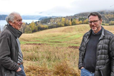VÅRFJOSHAUGEN: Bjørn Berg (t.h) har store planer om boligbygging på Hjuksebø. Hele 100 mål har han til disposisjon i Vårfjoslia (bak), men i påvente av at arealplanen for Notodden skal rulleres i 2022, starter han opp med en privat regulering på Vårfjoshaugen allerede nå. Her sammen med Nils Angard.
