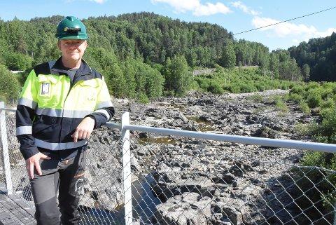 HAR ET ANSVAR: Det var tørt og fint og god temperatur i kulpene i Tinnåa ved Lienfossbrua fredag morgen. En time senere så det ganske annerledes ut da Jarle Andersen, HMS-leder hos Hydro Energi i Telemark åpnet dammen halvveis.