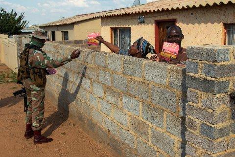 Koronaviruset har fått fotfeste i Afrika, og flest smittetilfeller er det foreløpig i Sør-Afrika. Her fra Soweto utenfor Johannesburg, hvor en soldat deler ut flygeblader med informasjon om koronaviruset.