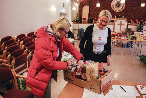 VIKTIG støtte: Bente Skauff er en av mange som har fått julemat og julegodt på Frelsesarmeen denne uken. – Mat herfra kommer godt med, sier hun. Matmor Guro Fossnes fyller matkassa. FOTO: Tone Finsrud