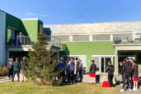OVERRASKES: Her marsjerer spillerne til Nøtterøy Håndball inn og overrasker ildsjel Henrik Møyland (på terrassen) på Smidsrød Helsehus. Se video av opptrinnet lenger ned i saken.