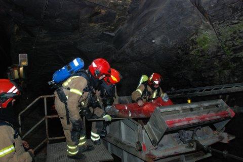 """Brannøving: Den """"skadde"""" blir frakta ut på båre i vogna som går på ein 400 meter lang skinnebane skrått opp att i dagen frå 75 meters djup i Skiferberget."""