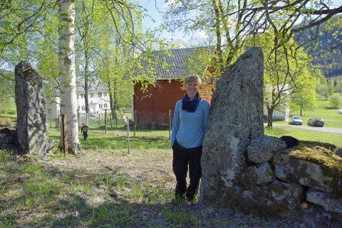 Bergliot Hedda Lunde ved den gamle steinporten ned til Lunde, merkt med AL 1796.