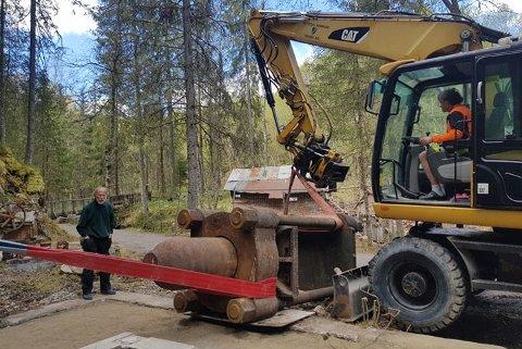 TUNGTLØFT: Kommunens gravemaskin greier så vidt å løfte kruttpressa på plass. Harald Aasen fra dugnadsgjengen følger med.
