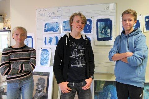 BLÅ UTSTILLING: Oda Skovholt (13), Jonas Skogstad og Johannes Østnes (begge 15) foran noen av bildene laget i teknikken cyanotype. Eivind Finstad, Katja Yakoleva og Jack Mcconnel Thommessen var ikke til stede da bildet ble tatt.