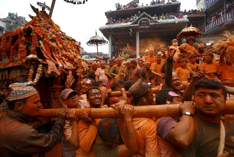"""Devotees celebrate """"Sindoor Jatra"""" vermillion powder festival at Thimi, in Bhaktapur April 15, 2015. The festival is celebrated by singing, dancing, playing traditional instruments, carrying chariots of various deities around the town, offering prayers and throwing vermilion powder over each other to mark the Nepalese New Year and the beginning of the spring season in the country. REUTERS/Navesh Chitrakar      TPX IMAGES OF THE DAY"""
