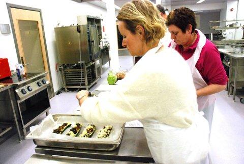 Julianne Lie drysser mozarella over fylte squash som skal gratineres.